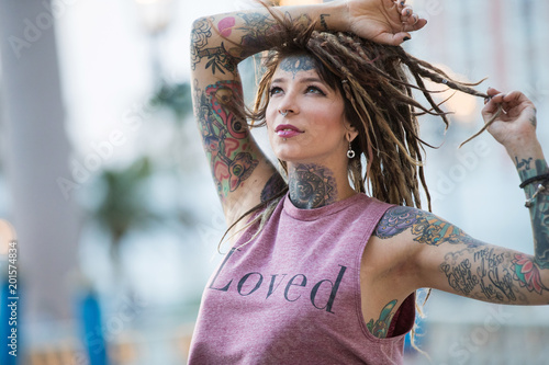 Photo  Beautiful hippie girl with tattoos and dreadlocks