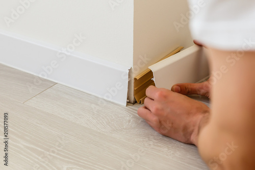 Mans hands putting white baseboard Wallpaper Mural