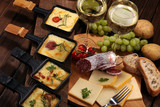 Fototapeta Tęcza - Delicious traditional Swiss melted raclette cheese on diced boiled or baked potato.