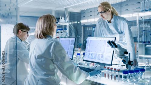 Carta da parati In Modern Laboratory Senior Female Scientist Discusses Work with Young Female Assistant