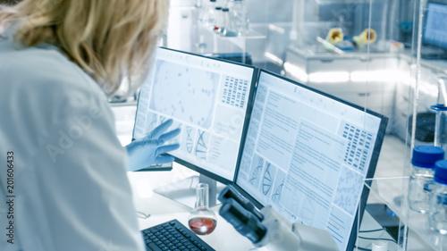 Carta da parati Senior Female Scientist Discusses Scientific Data with Her Laboratory Assistant