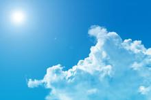 日差しが強い夏の青空と透ける白い入道雲