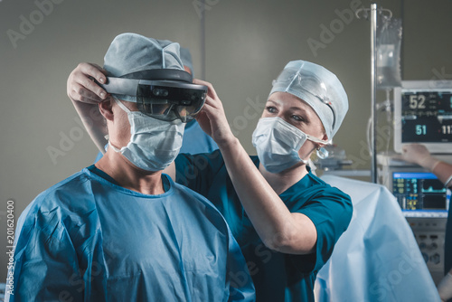 Fotografía  Nurse assisting surgeon with mounting augmented reality holographic hololens gla
