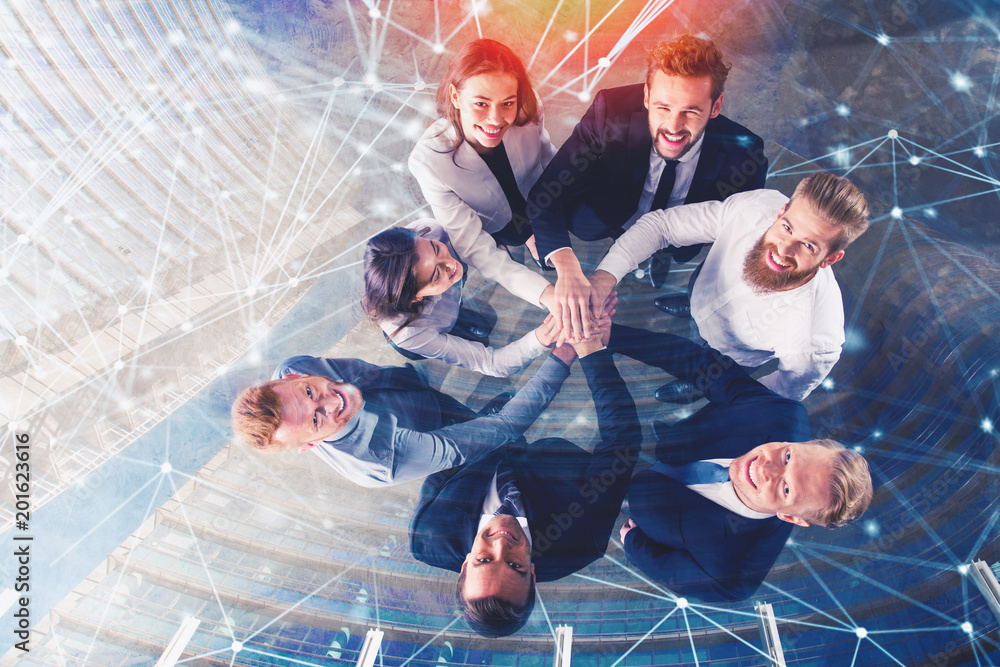 Fototapeta Business people putting their hands together with internet network effects. Concept of integration, teamwork and partnership. double exposure