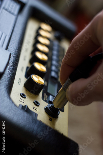 Photo Closeup of man's hand plugging jack into the guitar amplifier