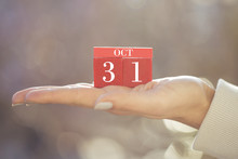 The Woman Is Holding A Red Wooden Calendar. Red Wooden Cube Shape Calendar For OCT 31 With Hand