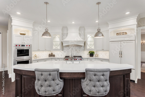 Obraz Kitchen in new luxury home: large, elegant kitchen, with pendant lights, and huge island, with refrigerator and double ovens.  - fototapety do salonu