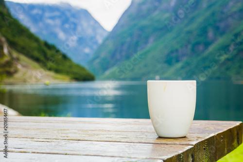 Mug on wooden table, fjord norwegian landscape