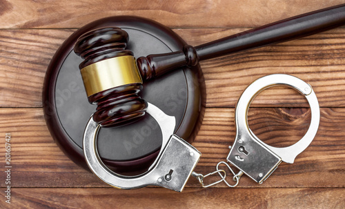 Gavel with stand and handcuffs on the wooden background Fototapeta