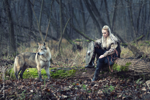 Photo  Viking warrior woman with ax and shield, next to an wild wolf, looking for dange