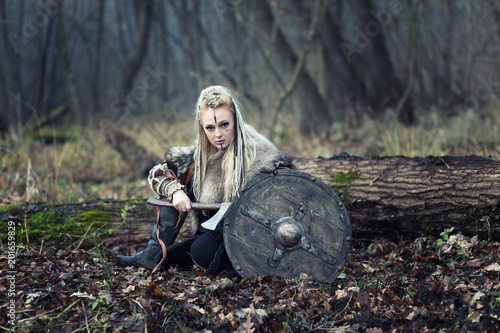 Photo  Portrait of dangerous Viking warrior woman with ax and shield in the forest read