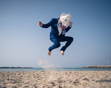 Stylish Man In Funny Mask And Suit Jumps On Beach