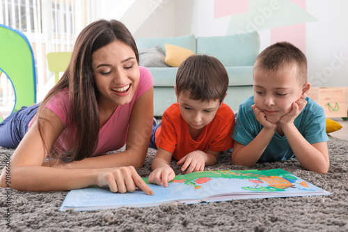 Photo Two little boys reading book with nanny at home