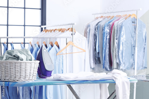 Fotografie, Obraz Wicker basket with clothes on ironing board at dry-cleaner's