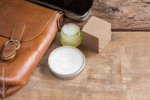 Fotografia  old genuine leather bag on wooden table prepare to clean and care with wax
