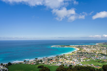 Relaxing At The Blue Bass Strait Sea And Enjoying A Warm Sunny Beach View Over Blue Sky Water Of Great Ocean Road With A Few Clouds Horizon Over Small Town Apollo Bay, Melbourne, Victoria, Australia