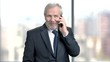 Confident mature businessman with mobile phone. Elderly bearded businessman talking on smartphone on blurred background. People, business and technology concept.