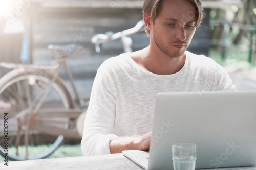 Cuadros en Lienzo Young male freelancer sitting in cafe working in laptop