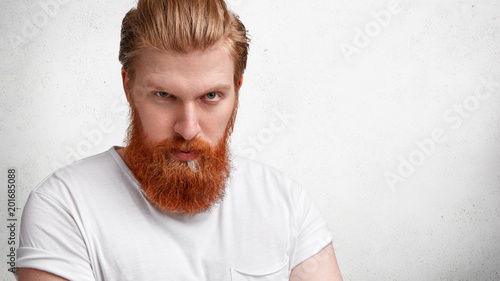 Fotografía  Horizontal shot of strict fashionable male with red long beard and stylish haird