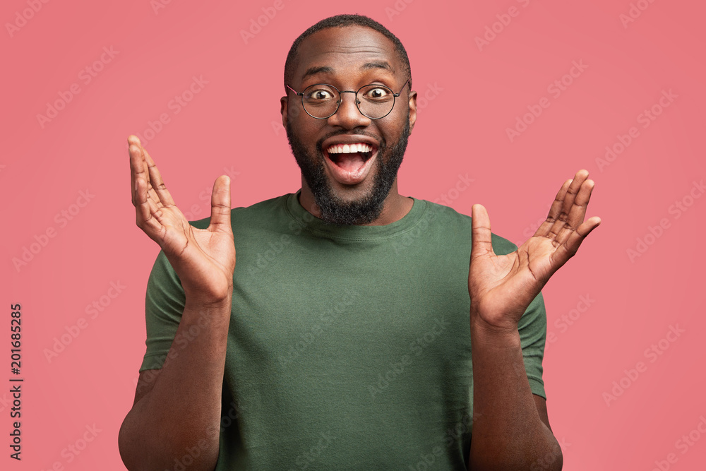 Fototapeta Overjoyed attractive dark skinned male student finds out about successful graduation, gestures with hands and expresses happiness, isolated over pink background. Positive African businessman