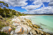 Beautiful sunny summer coast view from Bay Of Fires to blue Tasman Sea with crystal clear water surrounded by red orange colorful shore rocks and white sandy beach, Binalong Bay, Tasmania, Australia