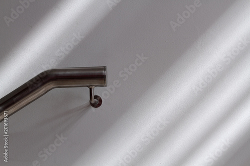 Steely handrail and light rays on a wall Wallpaper Mural