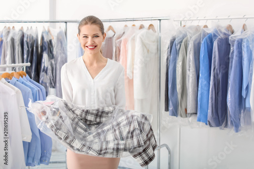 Fotografia, Obraz Young woman holding hanger with clothes in plastic bag at dry-cleaner's
