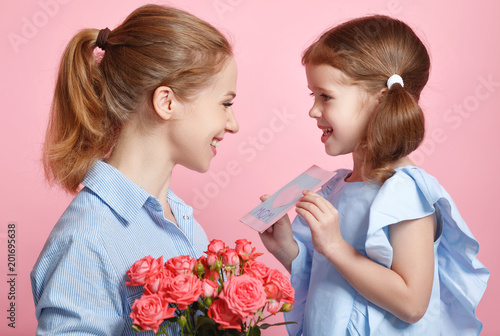 In de dag Barcelona concept of mother's day. mom and child with flower on colored background