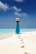 Attraktive Frau im blauem Kleid genießt ihren tropischen Strandurlaub