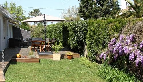 terrasse en bois exotique et salon de jardin près d\'une haie ...