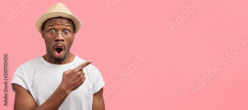 Horizontal studio shot of greatly surprised mixed race male wears stylish hat and casual white t shirt, advertises something with amazed expression, feels excited, blank copy space for your text
