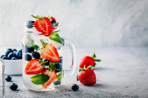 Infused detox water with blueberry, strawberry and mint. Ice cold summer cocktail or lemonade.