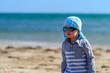 Cute boy in sunglasses walking on beach