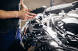 Auto mechanic testing electrical system on automobile