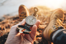 Compass Closeup In A Traveler Hand. POV View Of Hiking Boots. Blurred Background. Flare Effect
