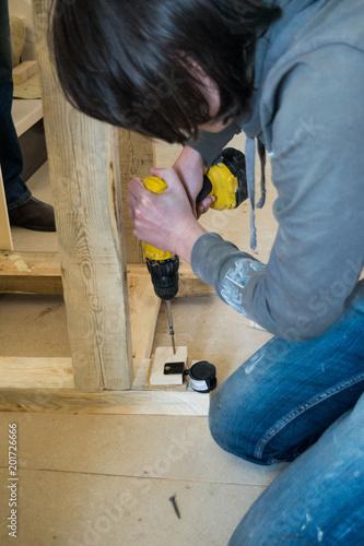 Fototapeta A young man with an electric screwdriver obraz na płótnie