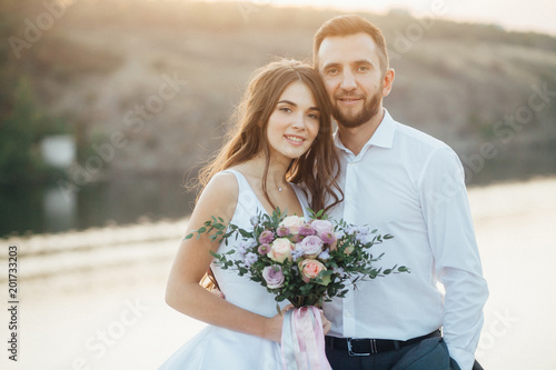 Fotografie, Obraz Lovely wedding couple at sunset looking at camera and smiling
