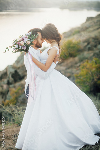 Fotografía  Wedding couple embrance at the walk with mountain and river at the background