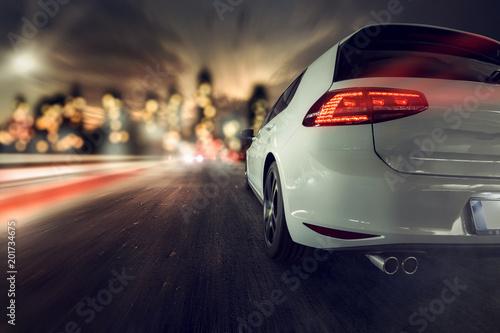 Fotografia, Obraz  schnelles Auto fährt auf Stadt zu