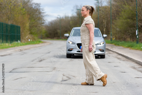 Woman crossing the road, with a car approaching behind her Fototapeta
