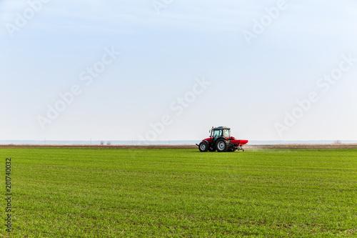 Foto  Farmer in tractor fertilizing wheat field at spring with npk