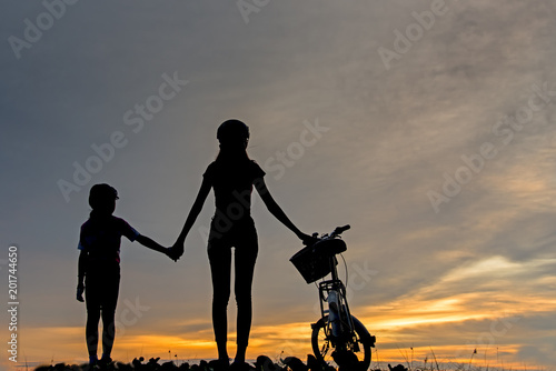 Fotografia, Obraz  Silhouette biker lovely family at sunset over the ocean