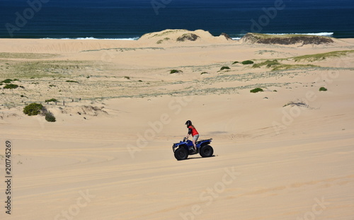 Happy quad bikers driving in sand dunes at Anna bay (Newcastle, NSW, Australia). Active people in outdoor activity driving quad on coastal desert beach.