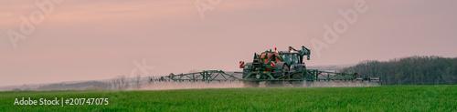 Photo  Ackerbau - Landwirt bei Pflanzenschutzmaßnahmen im Getreide am Abend, Banner