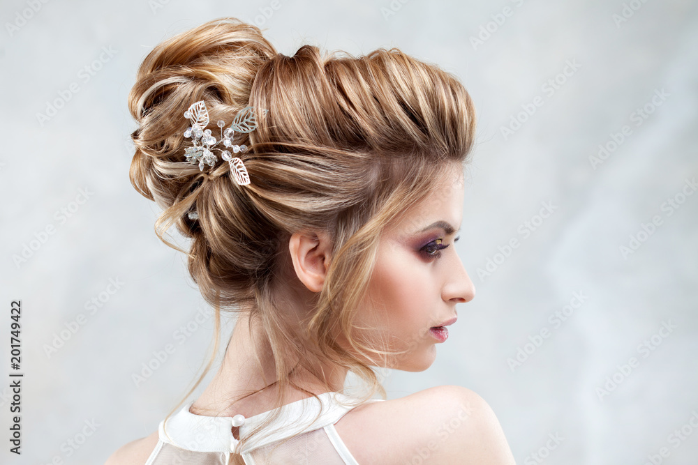 Fototapeta Young beautiful bride with an elegant high hairdo. Wedding hairstyle with the accessory in her hair