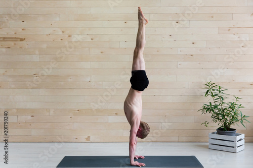 Photo Sporty man practices yoga handstand asana Adho Mukha Vrikshasana at the yoga studio