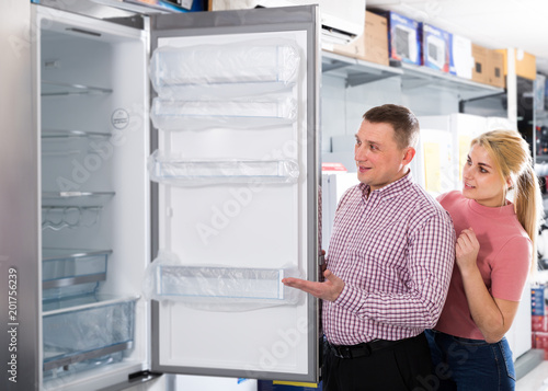 Couple looking new refrigerator in household appliances shop Fototapete