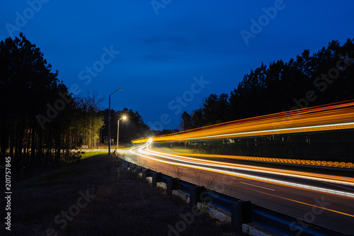 Motion blur of bus on city street at dusk Canvas Print