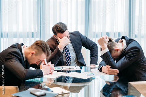 business failure. prospective bankruptcy. stressed stunned crushed defeated team of company executives or managers sit in the boarding room