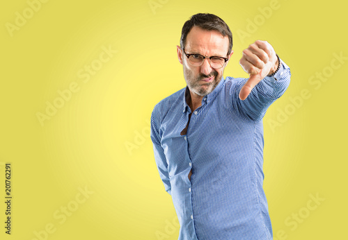 Handsome middle age man showing thumbs down unhappy sign of dislike, negative ex Tablou Canvas